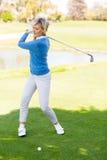 Weiblicher Golfspieler, der einen Schuss nimmt Stockfotos
