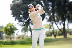 Weiblicher Golfspieler, der einen Schuss nimmt Stockfotografie
