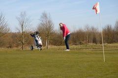 Weiblicher Golfspieler, der Golfball auf Schale mit Flagge abbricht Stockfoto