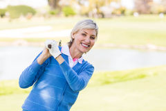Weiblicher Golfspieler, der ihr Vereinlächeln halten steht Stockfoto