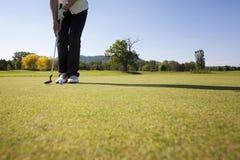 Weiblicher Golfspieler, der Kugel setzt. Lizenzfreie Stockfotos