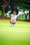 Weiblicher Golfspieler mit dem Putter, der hockt, um das Grün zu analysieren Stockfotografie