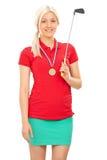 Weiblicher Golfspieler mit einer Medaille, die einen Golfclub hält Stockbild