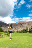 Weiblicher Golfspieler schlägt Golfball Lizenzfreie Stockfotos