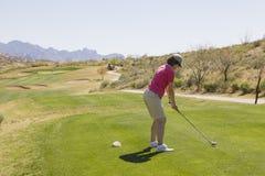 Weiblicher Golfspieler an T-Stück Kasten lizenzfreie stockfotografie