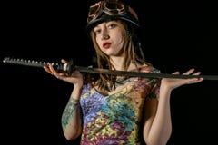 Weiblicher gotischer Krieger in den alten Versuchsgläsern, die mit katana Klinge aufwerfen Lizenzfreies Stockbild