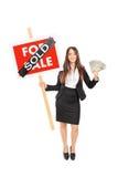 Weiblicher Grundstücksmakler, der ein Verkaufszeichen ein Geld hält Lizenzfreie Stockfotos