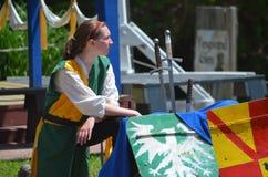 Weiblicher Gutsherr, der Jousters am Renaissance-Festival unterstützt Lizenzfreie Stockbilder