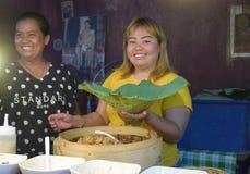 Weiblicher Händlerverkaufsreis in den Lotosblättern lizenzfreie stockfotografie