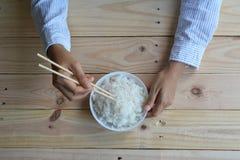 Weiblicher Handgriff Reis in der weißen Schüssel Stockfotos