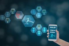 Weiblicher Handholding Smartphone, zum des Preises für Angebot, über drahtloses Netzwerk auf blauem bokeh Hintergrund mit Auktion stockbild