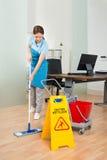 Weiblicher Hausmeister Cleaning Hardwood Floor im Büro lizenzfreies stockbild