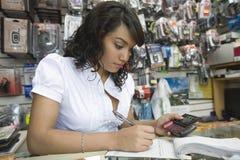 Weiblicher Herstellungsbill at mobile store Stockfoto