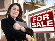Weiblicher hispanischer Immobilienmakler, Zeichen und Haus Stockbild