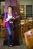 Weiblicher Hochschulstudent, der in der Bibliothek steht lizenzfreies stockbild