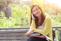 Weiblicher Hochschulstudent, der ihr Telefon, sitzend auf Holzbank in einem Park verwendet Lizenzfreies Stockfoto