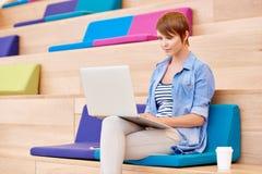 Weiblicher Hochschulstudent im bunten öffentlichen Platz, der an L arbeitet Lizenzfreie Stockfotografie