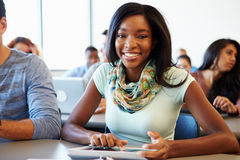 Weiblicher Hochschulstudent Using Digital Tablet im Klassenzimmer lizenzfreie stockfotografie