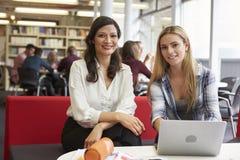 Weiblicher Hochschulstudent Working In Library mit Tutor stockfotografie