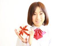 Weiblicher hoher Schüler, der ein Geschenk anbietet Stockbilder