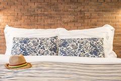 Weiblicher Hut und Kissen auf dem Bett eines Hotelzimmers Stockfotografie