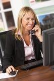 Weiblicher Immobilienmakler, der am Telefon am Schreibtisch spricht Lizenzfreie Stockfotos
