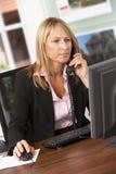 Weiblicher Immobilienmakler, der am Telefon am Schreibtisch spricht Lizenzfreie Stockbilder
