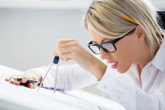 Weiblicher Ingenieur, der an Plan mit Zeichenzirkel arbeitet Stockfotografie