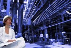 Weiblicher Ingenieur mit Lichtpausen auf Fabrik stockbild