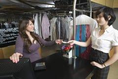 Weiblicher Inhaber, der den Empfang vom Kunden in der Wäscherei empfängt Lizenzfreie Stockfotos