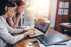 Weiblicher Innenarchitekt, der mit aufpassenden Bildern eines Kunden unter Verwendung des Laptops sitzt am modernen Studio arbeit Lizenzfreie Stockfotografie