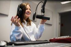Weiblicher Jockey Communicating On Microphone im Radiostudio stockfotografie
