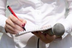 Weiblicher Journalist an der Pressekonferenz, die Anmerkungen schreibend und halten Mikrofon Stockfotografie