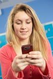 Weiblicher Jugendkursteilnehmer, der Handy verwendet Stockbild