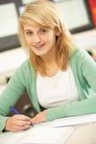 Weiblicher Jugendkursteilnehmer, der im Klassenzimmer studiert Lizenzfreie Stockfotografie