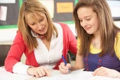 Weiblicher Jugendkursteilnehmer, der mit Lehrer studiert Stockfotos