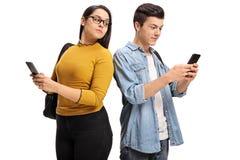 Weiblicher jugendlich Student, der am Telefon eines männlichen jugendlich Studenten späht Stockbild