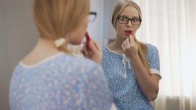 Weiblicher Jugendlicher in den Gläsern, die auf erstem rotem Lippenstift nahe dem Spiegel, wachsend versuchen heran stock video
