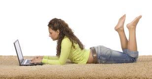 Weiblicher Jugendlicher, der auf dem Teppich mit Laptop liegt Stockfoto
