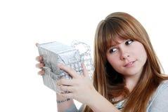 Weiblicher Jugendlicher, der ein Weihnachtsgeschenk rüttelt Lizenzfreie Stockbilder