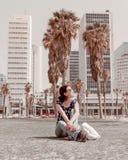 Weiblicher junger Tourist sitzt vor Geschäftsgebäuden in der Mitte der Stadt Stockfotografie