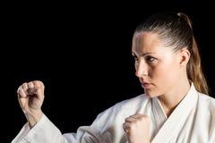Weiblicher Kämpfer, der Karateposition durchführt stockbild