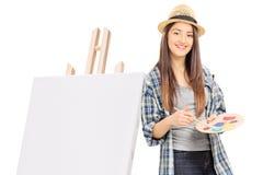 Weiblicher Künstler, der auf einem Segeltuch sich lehnt Stockbild
