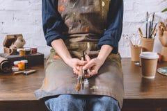 Weiblicher Künstler, der auf Tabelle sitzt und Bürsten hält Lizenzfreies Stockfoto