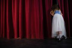 Weiblicher Künstler, der durch den roten Vorhang späht lizenzfreie stockfotografie