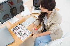 Weiblicher Künstler, der am Schreibtisch mit Computern im Büro sitzt Stockfotos