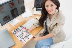 Weiblicher Künstler, der am Schreibtisch mit Computern im Büro sitzt Stockbilder