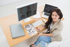 Weiblicher Künstler, der am Schreibtisch mit Computern im Büro sitzt Lizenzfreies Stockbild