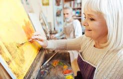 Weiblicher Künstler, der Zeit in der Malklasse verbringt Stockbild