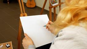 Weiblicher Künstler zeichnet eine Bleistiftskizze im Kunststudio Stockfotos